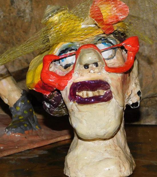 Tête de femme à chapeau jaune et lunettes rouges